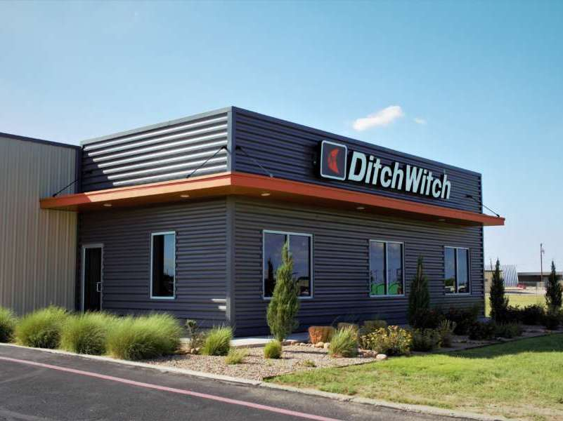 Ditch witch against a blue sky with lush green landscaping
