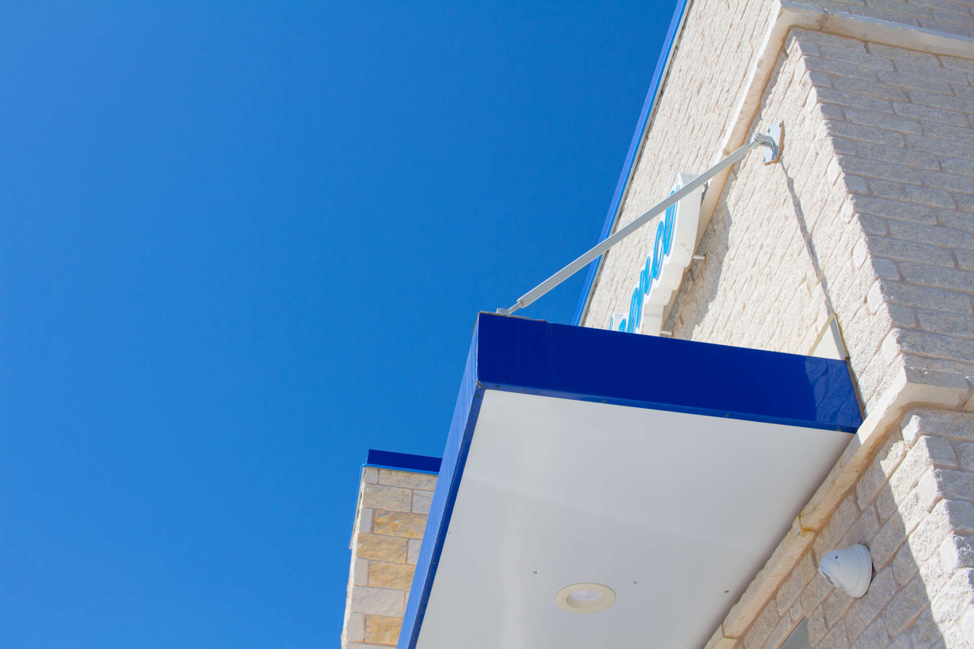 Water Still Custom Awning with brace and a clear blue sky