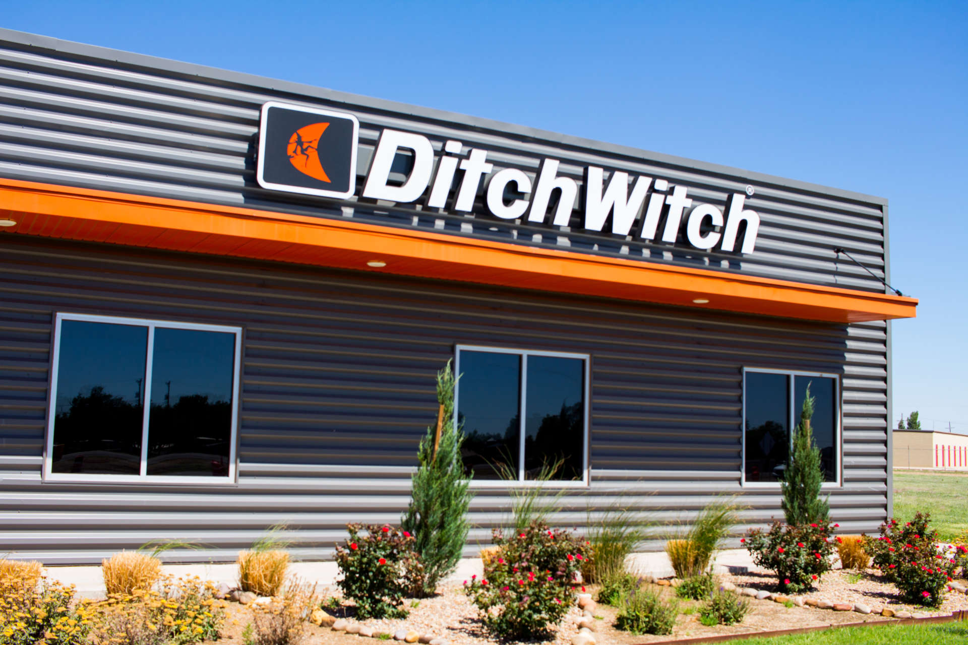 Ditch Witch from the front of building with rocks and landscaping
