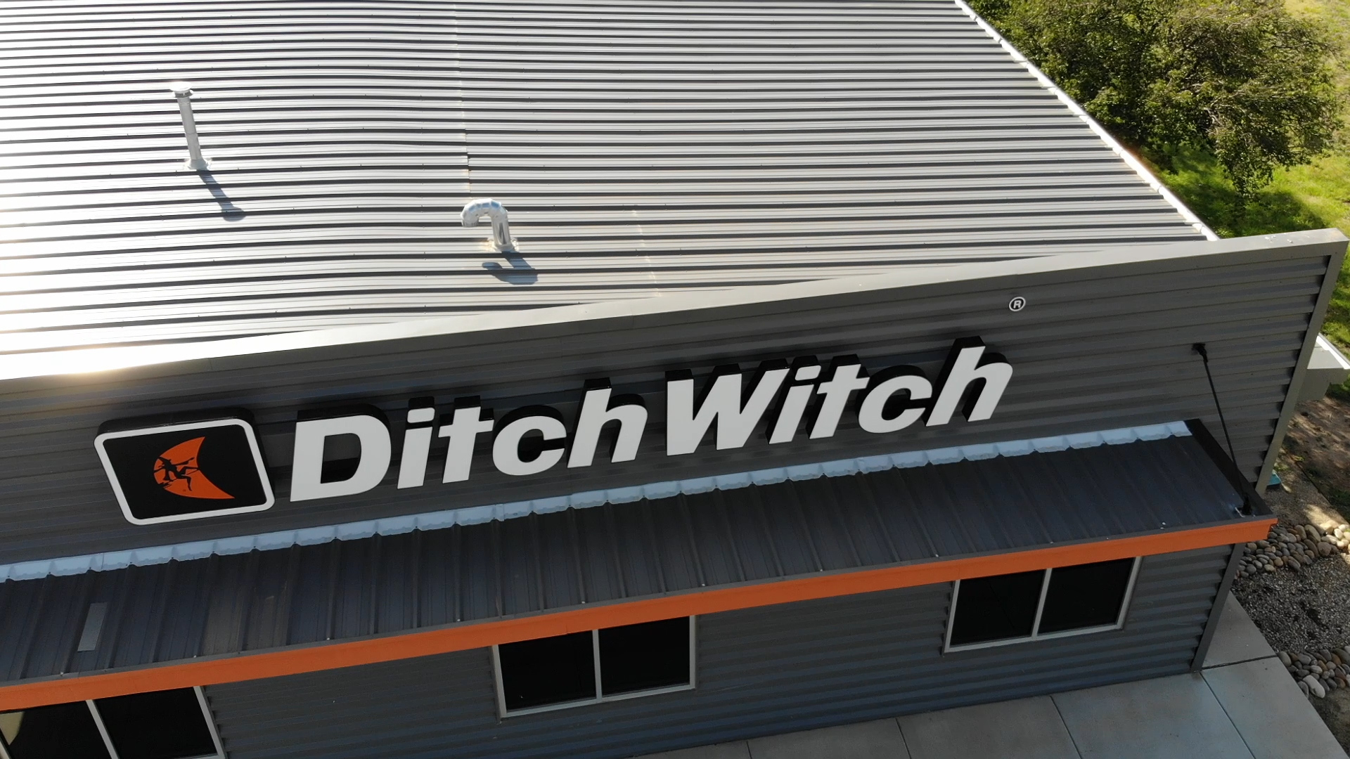 Ditch Witch roof from the air with sun shining on the metal