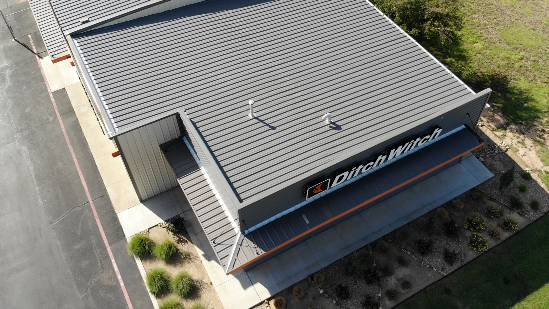 Ditch witch gray roof from drone angle with signage and landscaping