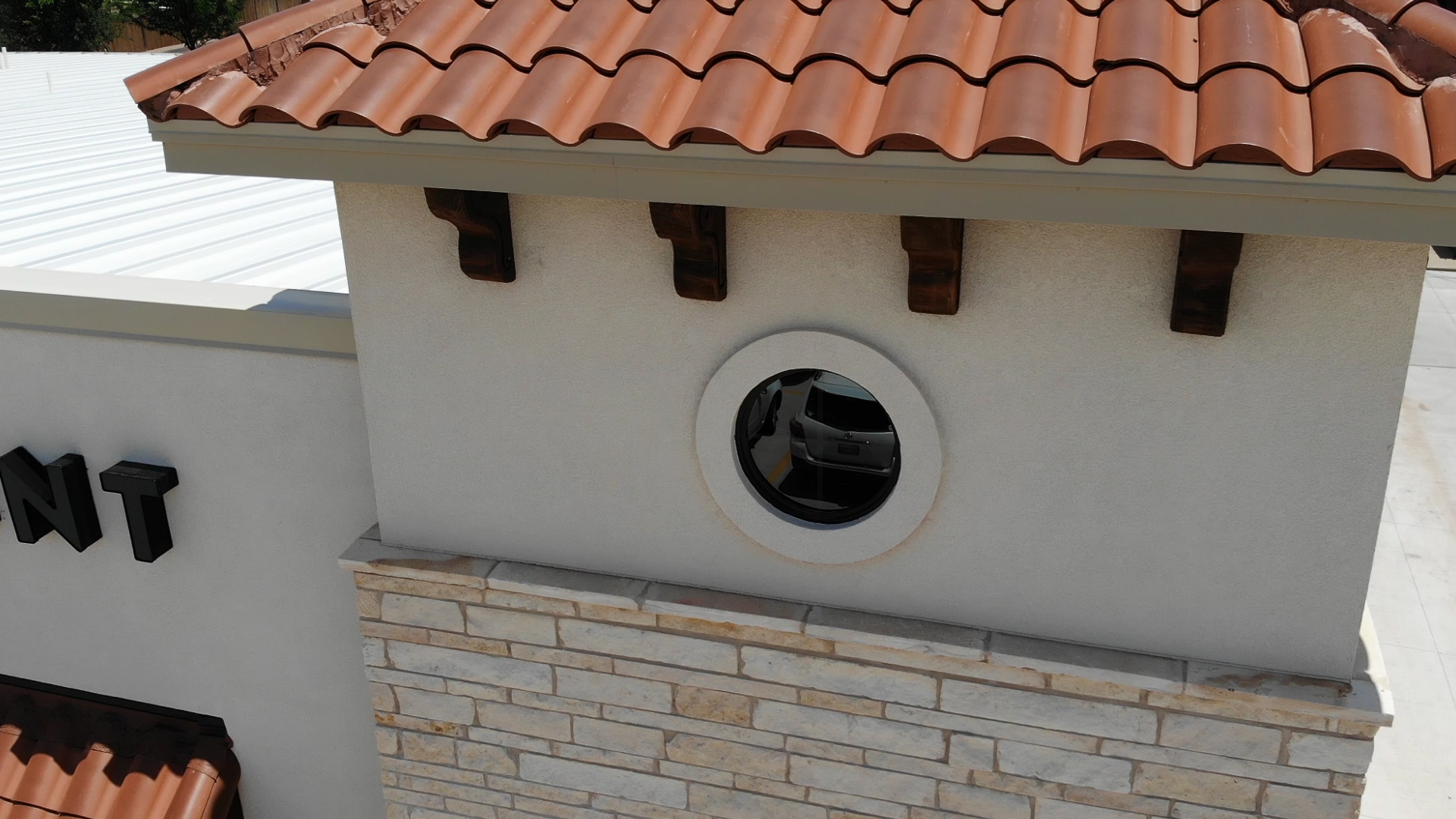 shopping center round accent window above masonry
